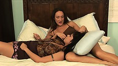 Two gorgeous babes get down on the sheets to make out and fuck
